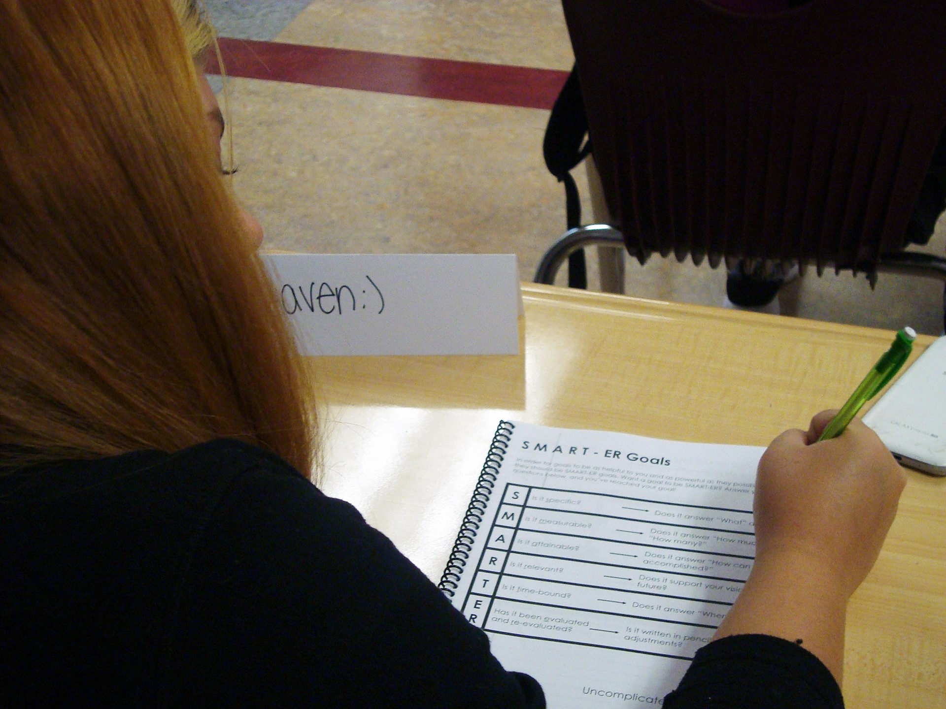 A 9th grader looks over her Start Your Story work book.  SMART goals seem cool!