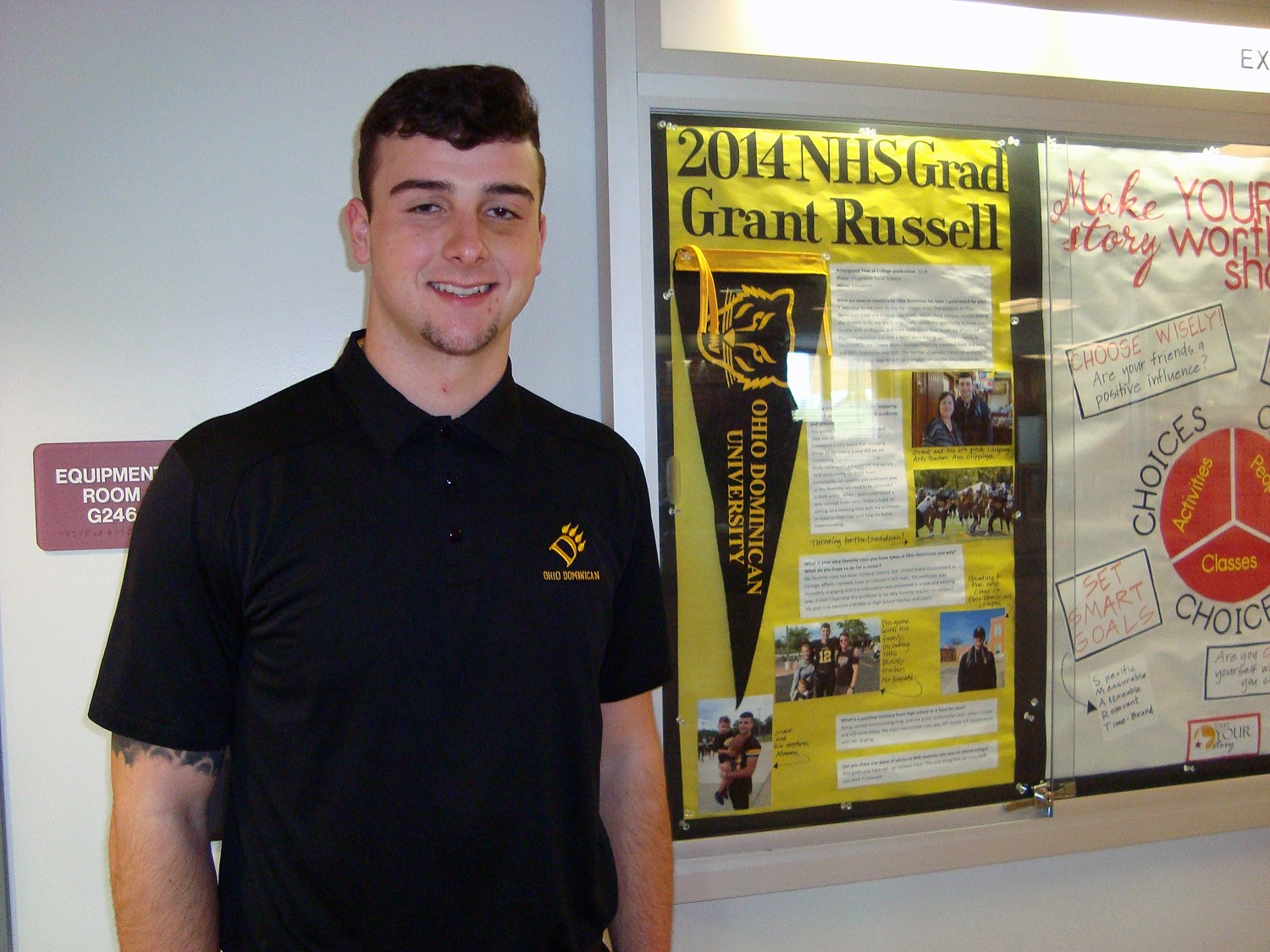NHS Grad and current Ohio Dominican student, Grant Russell checks out his panel on the Academic Wall