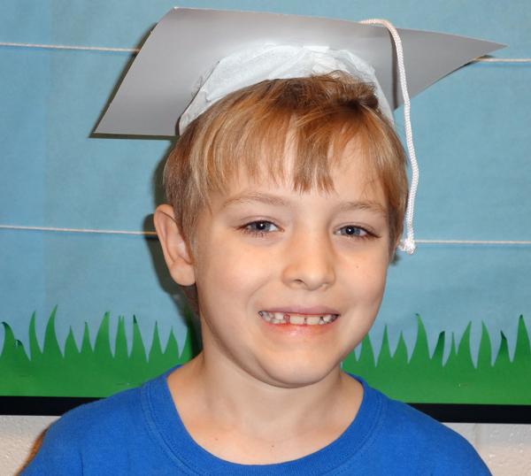 Nearly 600 2nd graders get a graduation cap photo taken to be put in their PEAK week booklet